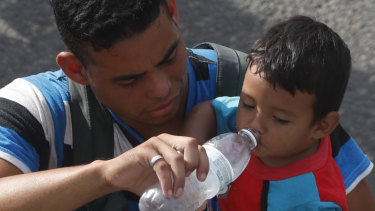 A man carrying a boy gives the child water while walking with a caravan of Central American migrants heading for the US.