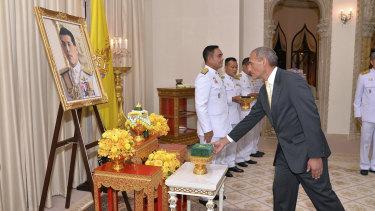 Craig Challen receives the Member of the Most Admirable Order of the Direkgunabhorn in front of a portrait of Thailand's King Maha Vajiralongkorn Bodindradebayavarangkun.