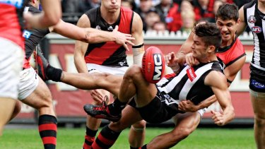 Bombers ruckman Paddy Ryder slings Magpie Sharrod Wellingham to the ground in a tackle.