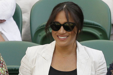 Meghan, Duchess of Sussex, left, smiles as she takes her seat on Court Number One to watch United States' Serena Williams play Slovenia's Kaja Juvan in a singles match during day four of the Wimbledon Tennis Championships in London, Thursday, July 4, 2019. (AP Photo/Tim Ireland)