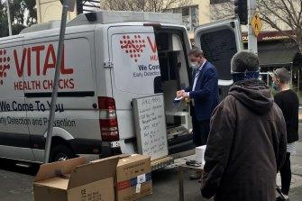 Ricky Nixon on Bay Street in Port Melbourne in 2020 selling PPE alongside his health company van.