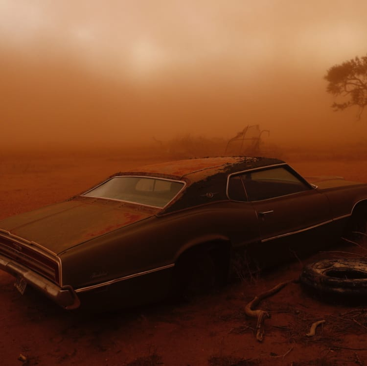 A rusting Ford Thunderbird in Texas is swallowed by red dust created when topsoil is ripped from ploughed fields and lifted into the sky.