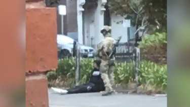 A counter-terrorism officer stands guard over the arrested man.