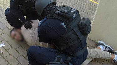 Police arrest a man outside Centrelink in Leichhardt.