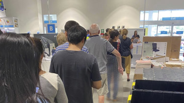 People lining up at an Officeworks store, as many preparing to begin working from home over coming days.