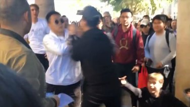 The first punch was thrown when the protest organiser approached two students after one of them stole his megaphone and threw it.