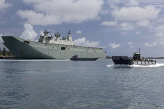 HMAS Adelaide with a  landing craft.