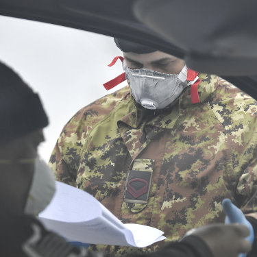 An Italian Army soldier checks paperwork at a cordon in Italy's north.