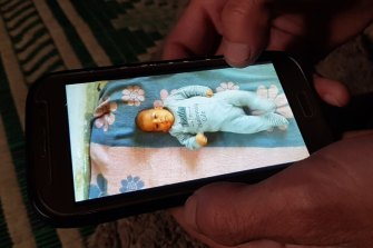 'Abu Hazem' cradles a photograph of his seven-month-old son who froze to death in his sleep in February.