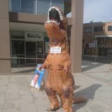 Peter Thompson wearing the dinosaur suit which bears the name 'Craig Kelly Denialosaur'.