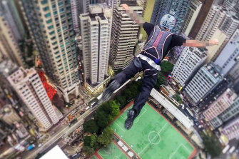 The man BASE jumping from a building in Hong Kong.