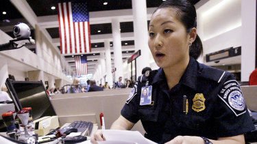 A US Customs and Border Protection officer checks the passport and paperwork of a visitor at Los Angeles International Airport.
