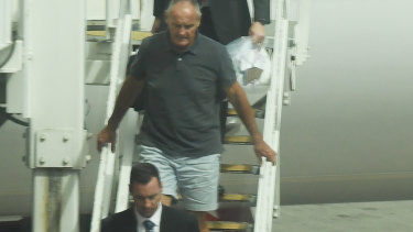 Chris Dawson is escorted by NSW Police detectives off a Qantas flight as he is extradited from the Gold Coast.
