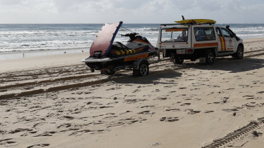 A surf life saving crew drives past the scene where the body of an infant was found at Surfers Paradise.