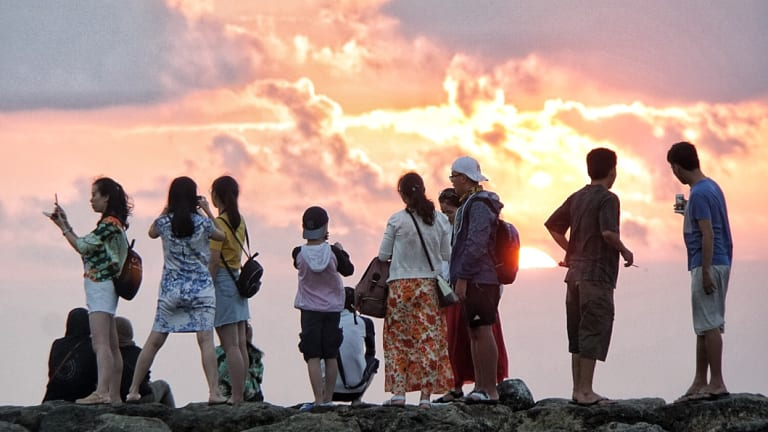 Chinese tourists watch the sunset on Kuta beach.