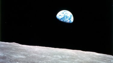 A photo of the Earth rising over the lunar horizon taken in 1968 by the first humans to venture beyond low Earth orbit.