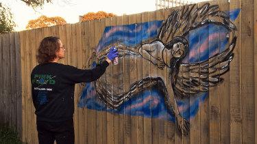 Miriam Fee creates work on a wooden fence.
