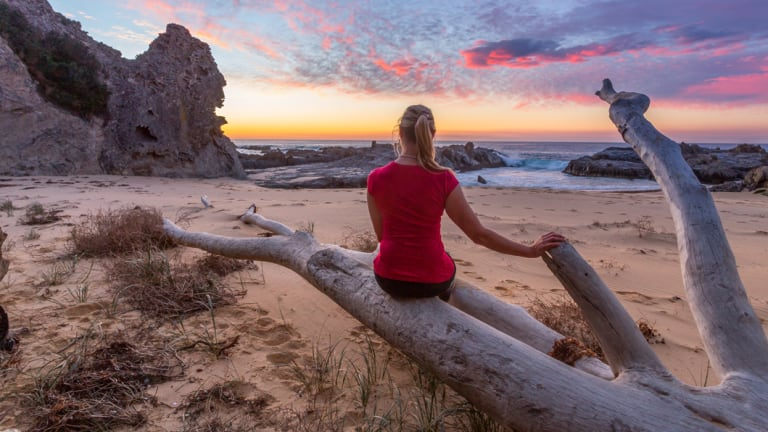 Landscape photographer Leah-Anne Thompson watches the sunrise at Queen Victoria Rock, near Narooma