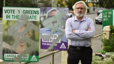Greens' Brisbane candidate Andrew Bartlett next to vandalised placards on Sandgate Road in Clayfield.