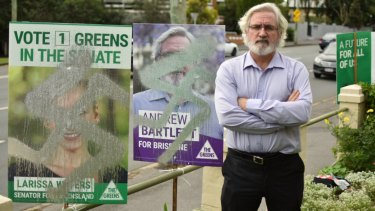 Greens' Brisbane candidate Andrew Bartlett next to graffitied placards on Sandgate Road in Clayfield.