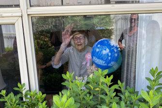 Gladys Nutbean waves to relatives through her window.