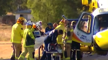Paramedics treat a woman who was impaled in an accident on the Warrego Highway.