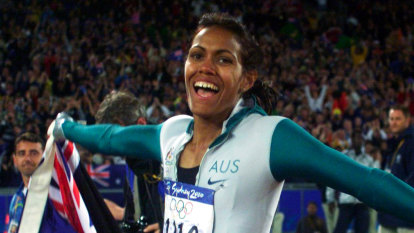 Cathy Freeman carries both the Aboriginal and the Australian flags during her victory lap.