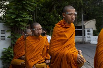 Buddhist monks wear face shields while collecting alms during a partial lockdown imposed due to the coronavirus in Bangkok, Thailand, on Monday, May 11.