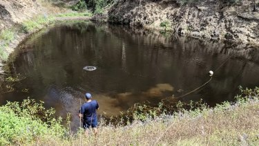 Police search one of the smaller dams in the area.