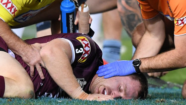 Michael Morgan with Maroons staff after taking a heavy blow to the head in Origin III.