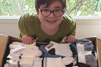 Benjy Orwin, 11, with some of the thousands of pairs of socks he has helped donate.