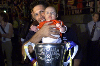 Chris Johnson with son Lachlan, pictured after the 2001 AFL grand final.