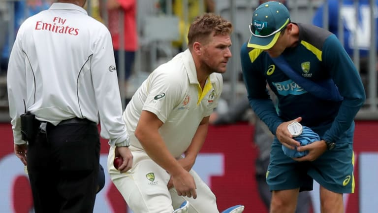 Cruel blow: Aaron Finch receives treatment on his injured finger before retiring hurt.