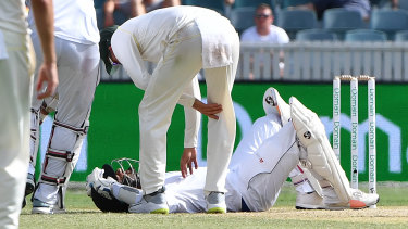 Man down: Sri Lankan batsman Dimuth Karunaratne on the ground after being hit in the head against Australia at Manuka Oval in February.