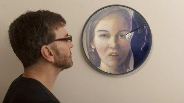Artist Darren Pryce with his portrait of Brittany Higgins.