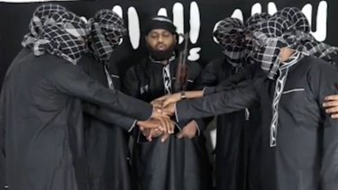 Image posted by Islamic State purports to show attackers in Sri Lanka standing before the terror group's flag.