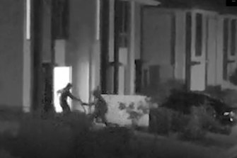 The two offenders can be seen running into the garage holding a firearm.