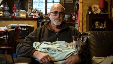 Manfred Zabinskas with the Kangaroo joey - Jess - who he cares for at his sanctuary after its rescue.