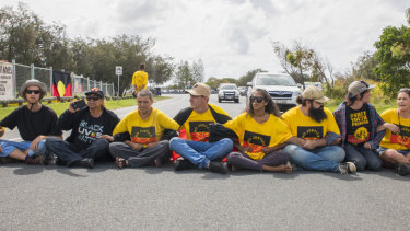 Protesters sit in the middle of the road in an attempt to stop the Queens Baton relay.