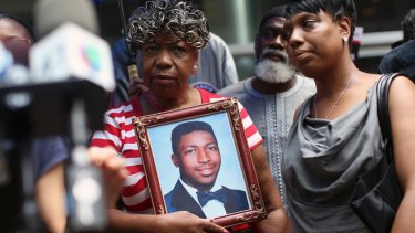 Gwen Carr, mother of Eric Garner, holds a photo of him during a news conference in 2015.