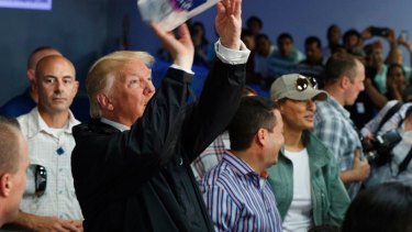 President Donald Trump tosses paper towels into a crowd in Puerto Rico last year following Hurricane Maria.
