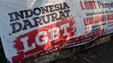 "FILE - In this March 17, 2016 file photo, a man walks past an anti-LGBT banner erected by an ultra-conservative Islamic group in Jakarta. Indonesia's Constitutional Court is considering whether to make gay sex a crime after accepting a judicial review petition from Islamic activists. A group calling itself the Family Love Alliance says an existing law that criminalizes sex between adults and minors of the same gender, and which mandates prison sentences of up to 15 years, should be amended to also apply to sexual acts between adults of the same gender. Rita Hendrawaty, chairwoman of the group, said Wednesday, Aug. 3, it was not trying to criminalize lesbian, gay, bisexual and transgender people. Letters on the banner read: ""Indonesia is on LGBT emergency"" and ""Gay people are contagious, save the young generation from LGBT people."" (AP Photo/Tatan Syuflana, File)"