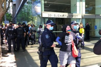 A protester is led away by police at a rally for transgender rights in Sydney. The event was prohibited by the NSW Supreme Court due to COVID-19 risk.