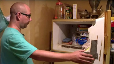 Adam Smith, 37, opens the freezer in his mother's St. Louis apartment.