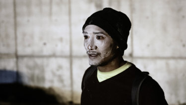A migrant with his face covered in white after receiving a treatment against tear gas.