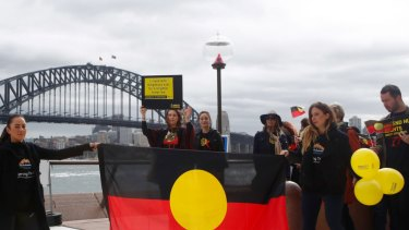 Cheree Toka and fellow demonstrators hold an Aboriginal flag during a demonstration in Sydney.