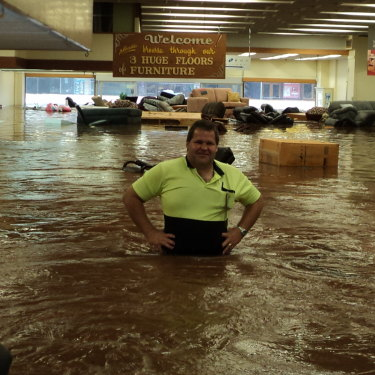 Rowes warehouse manager Wayne Miller stands waist deep in floodwater as furniture floats out to Russell Street.