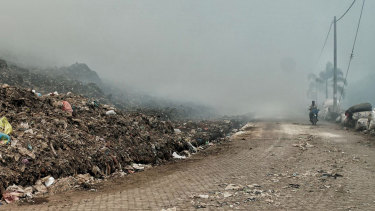 A scooter drove through the thick smoke from the Suwung dump site fire.