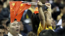 A child holds up Chinese national flags as she watches a pre-season NBA basketball game between the Brooklyn Nets and Los Angeles Lakers at the Mercedes Benz Arena in Shanghai, China.