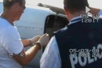 A handcuffed Santos assists police searching the plane at Jandakot Airport.